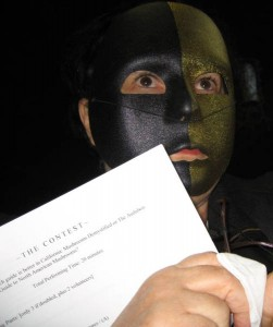 "Elinoar Shavit in a masked dramatic reading of ""The Contest"" at SOMA Camp"